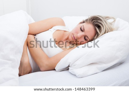 Portrait of woman with stomach ache lying on bed - stock photo