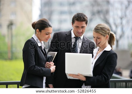 Portrait of women and a man in front of a laptop computer - stock photo