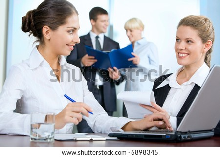 Portrait of women discussing their work on the background of business people