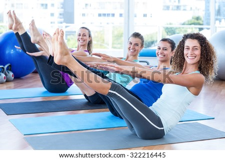 Portrait of women in fitness center doing boat pose on exercise mat - stock photo
