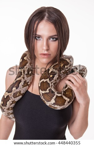 Portrait of women model posing in swimsuit with snake in studio. Smoky eyes make-up. Perfect body. Concept dangerous