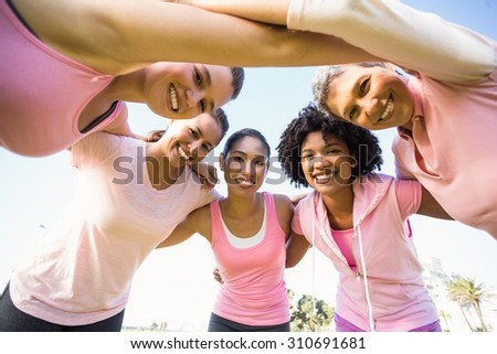 Portrait of women wearing pink for breast cancer with arms around in parkland - stock photo