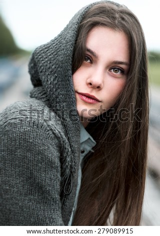 Portrait of wonderful woman in the hood in the spring park - stock photo