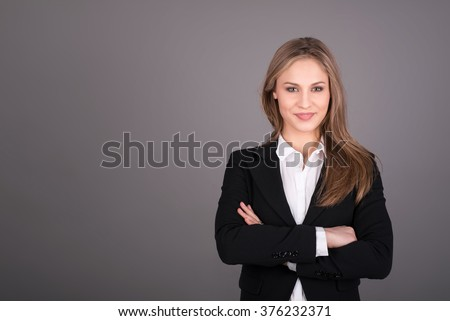 Portrait of wonderful young business woman on gray background with copy space - stock photo