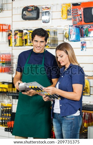Portrait of worker swiping credit card with woman holding screwdriver set at hardware store