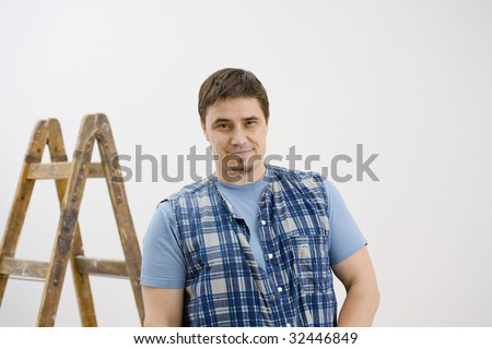 Portrait of worker wearing blue checked shirt, smiling. Isolated on white background. - stock photo