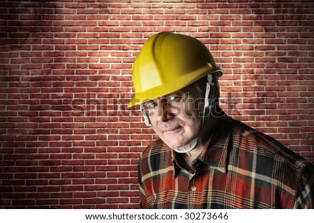 portrait of worker with an hardhat against a bricks wall - stock photo
