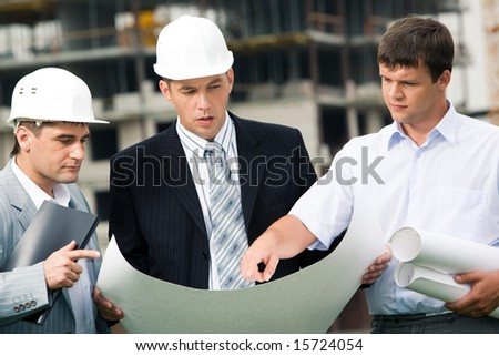 Portrait of workgroup of builders looking at new project in bossâ?? hands while one of men pointing at something - stock photo
