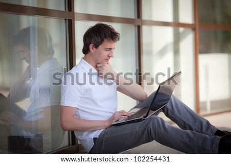 Portrait of working businessman with laptop outdoors