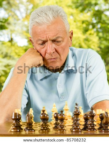 Portrait of worried elderly man playing chess outdoors.