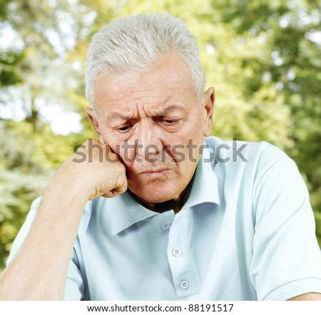 Portrait of worried senior man outdoors. - stock photo
