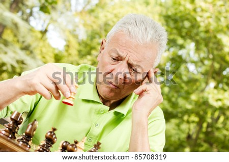 Portrait of worried senior man playing chess outdoors.