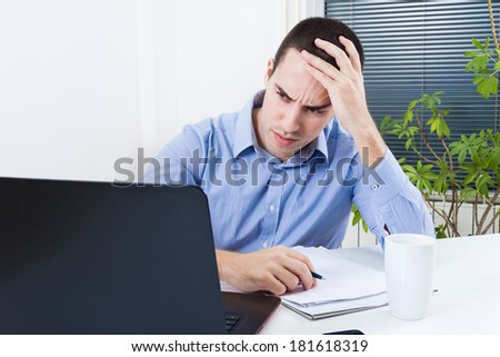 Portrait of worried young businessman sitting in front of laptop in his office