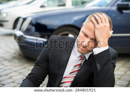 Portrait Of Worried Young Man With Damaged Car - stock photo