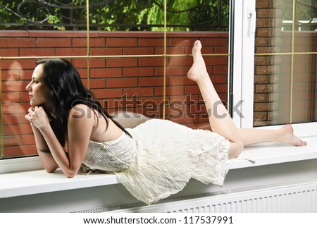 Portrait of yang and beautiful brunette in front of the window