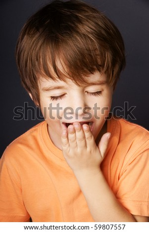 Portrait of yawning little boy, studio shot - stock photo