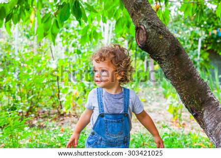 Portrait of 1 year old baby boy in the garden under a cherry tree.