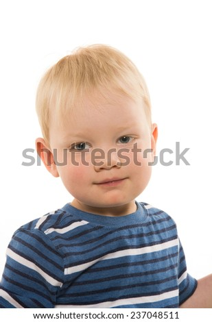 Portrait of 2-year-old blond boy with striped shirt on white background