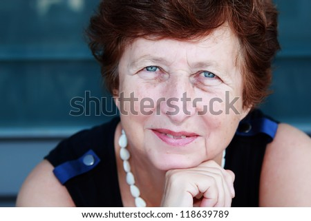 Portrait of 65-years-old beautiful woman outdoors - stock photo