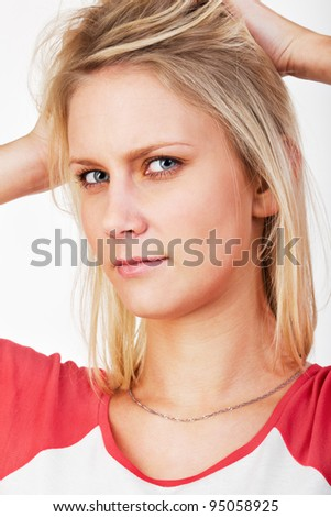 Portrait of 20 years old blonde woman with hand in her hair looking pensive. Studio shot against a white background. - stock photo