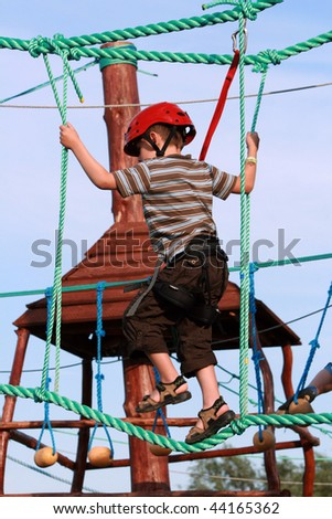 Portrait of 5 years old boy wearing helmet and climbing. Child in a wooden abstacle course in adventure playground - stock photo