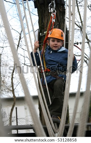 Portrait of 6 years old boy wearing helmet and climbing. Child in a wooden abstacle course in adventure playground - stock photo