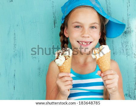 Portrait of 7 years old kid girl eating tasty ice cream on blue background - stock photo