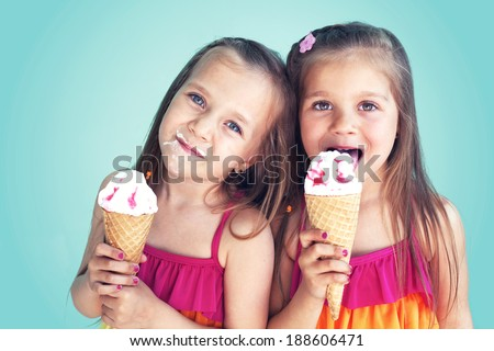Portrait of 5 years old kid girls eating tasty ice cream over blue - stock photo