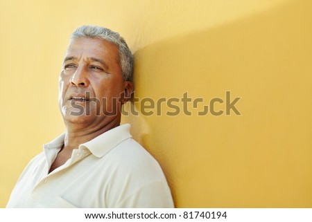 portrait of 50 years old latin american man having problems and leaning on yellow wall. Horizontal shape, copy space - stock photo
