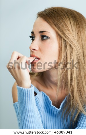 portrait of 30 years old woman biting her fingernails on cyan background. Vertical shape