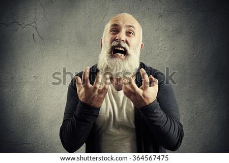 portrait of yelling senior man over grey background - stock photo