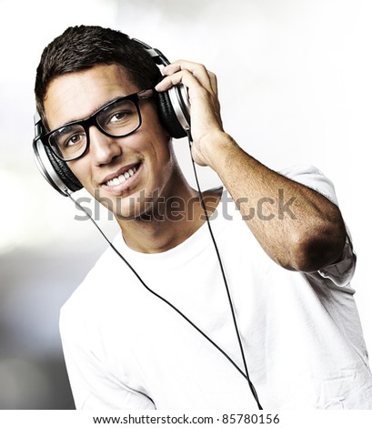 portrait of youn man with glasses listen to music in a living room - stock photo
