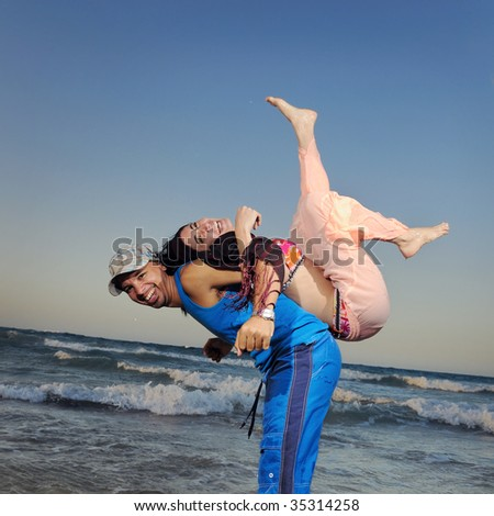 Portrait of young active happy couple enjoying the beach - stock photo