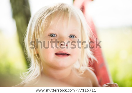 Portrait of young adorable girl under trees - stock photo