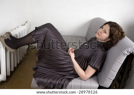 Portrait of young adorable pensive woman wearing grey dress sitting on sofa put her legs on radiator