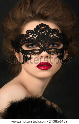 Portrait of young adorable woman wearing black party mask - stock photo