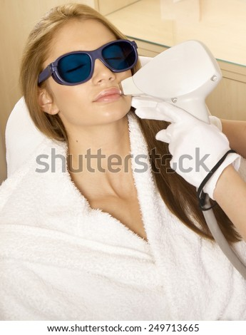 Portrait of young adult attractive and sensuality brunette pretty girl receiving laser therapy procedure. Woman getting laser face treatment in medical spa center skin rejuvenation concept - stock photo