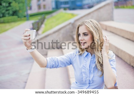 portrait of young adult business woman taking picture of themselves while sitting on steps of stairs outdoors in summer city park. lunch time. businesswoman make selfy or look at mirror. Well dressed. - stock photo