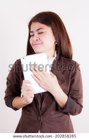 Portrait of young adult businesswoman smiling while using digital tablet.