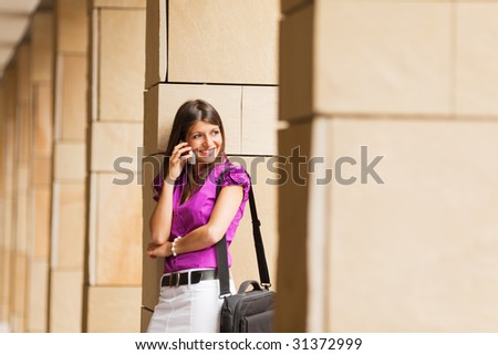 portrait of young adult businesswoman talking on the phone and leaning on column.