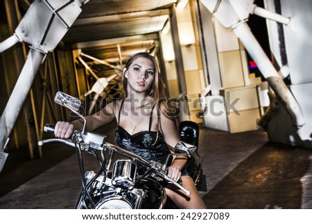 Portrait of young adult caucasian hot amazing  Biker girl in black leather shorts on a motorcycle Cute sexy woman with long brown hair looking at camera Empty copy space for inscription - stock photo