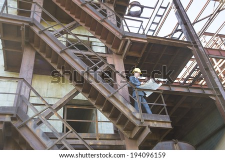 Portrait of young adult caucasian male architect in yellow hardhat  looking paper plan blueprint and writing with pen documents. Horizontal shape Well dressed engineer sitting on metal rusty ladder - stock photo