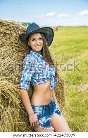 portrait of young adult Cowgirl stand near haystack against blue sky with clouds and summer field with hay Alone woman wear black hat , jeans shorts and stripped shirt - stock photo