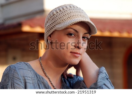 Portrait of  young-adult, during her treatment is wearing head cap - stock photo