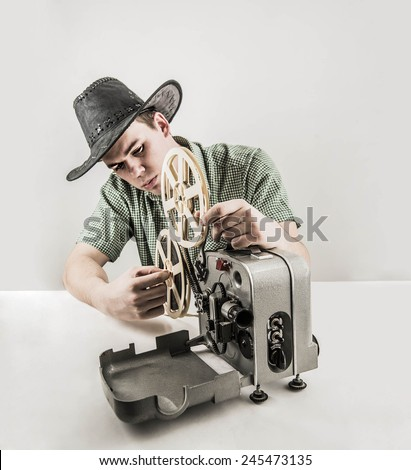 Portrait of Young adult handsome caucasian male man videographer holding a videography wear cowboy american hat old retro vintage style camera on gray background White and black film - stock photo
