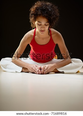 portrait of young adult latin american female sitting on white floor doing yoga exercise. Vertical shape, full length, front view, copy space - stock photo