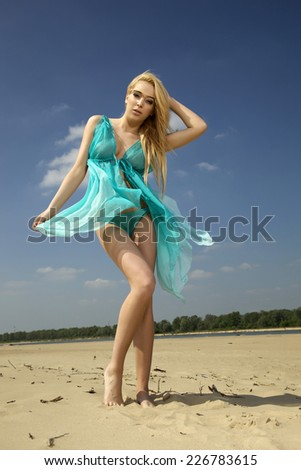 Portrait of young adult sensuality attractive and sexy pretty beauty blonde woman in blue dress dance on the beach - stock photo