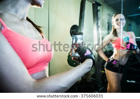 portrait of young adult woman with smartphone taking mirror reflection selfie in gym sport, fitness, lifestyle, technology and people concept. Image of small screen of mobile cell phone. Dusk light - stock photo