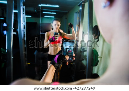 portrait of young adult woman with smartphone taking mirror reflection selfie in gym sport, fitness, lifestyle, technology and people concept Image of small screen of mobile cell phone Dusk light - stock photo