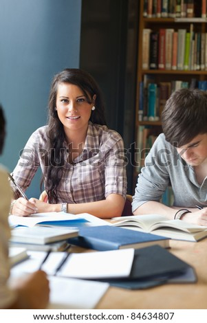 Portrait of young adults studying in a library - stock photo